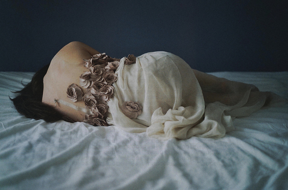 Young woman with bare back and long dark hair lying on bed covered in roses