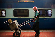 A porter walks past the Himsagar Express 6318 as it stops for 10 min at Ernakulam Stn., Cochin, Kerala on 9th July 2009.. .6318 / Himsagar Express, India's longest single train journey, spanning 3720 kms, going from the mountains (Hima) to the seas (Sagar), from Jammu and Kashmir state of the Indian Himalayas to Kanyakumari, which is the southern most tip of India...Photo by Suzanne Lee / for The National