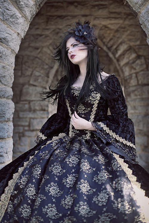 Young woman in black regency dress standing alone