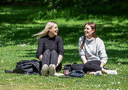 © Licensed to London News Pictures. 14/05/2020. London, UK. Enjoying the freedom. Two women picnic in the sunshine in Hyde Park after the Government relaxes the law on lockdown to let people spend more time outside to have picnics, sunbath and meet up with other people as weather experts predict a warmer week ahead. Photo credit: Alex Lentati/LNP