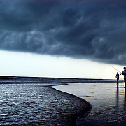 Fisherman cast as a storm front passes overhead at Wrightsville Beach, NC.
