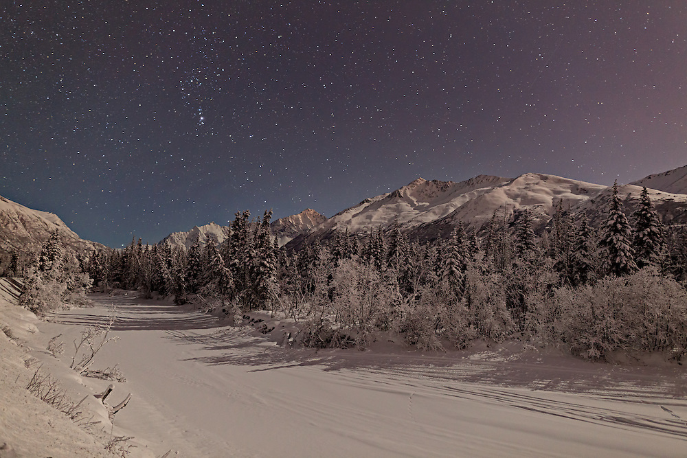 The Big Dipper constellation and shooting stars over the Chugach Mountains (Polar Bear Peak, Eagle Peak, and Hurdygurdy Mountain) along the frozen Eagle River in Chugach State Park in Southcentral Alaska. Winter. Evening.