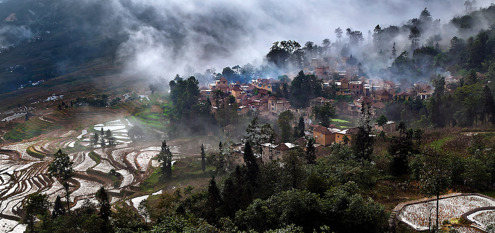 Mist lifting from the Hani ricefields and a village in Yuanyang, Yunnan, China.