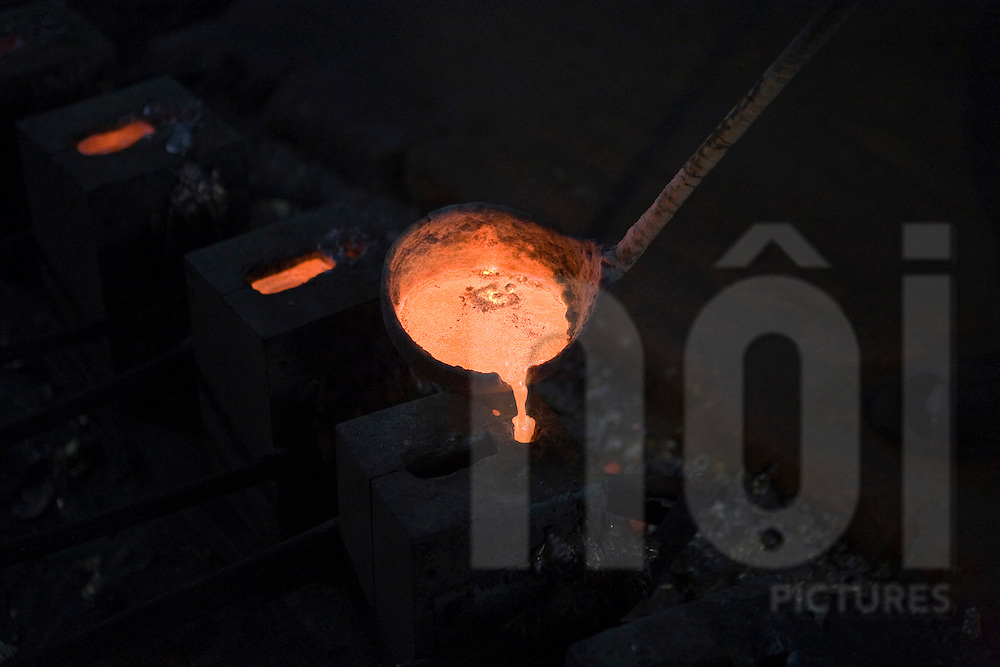 Color film photograph of molten metal in a ladel in a workshop of Dai Bai bronze casting craft village, Bac Ninh Province, Hanoi outskirts, Vietnam, Southeast Asia
