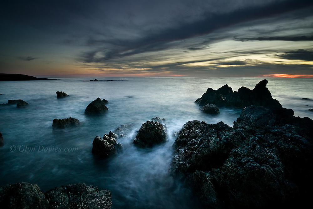 Gentle waves flow around the rocks at sunset at this rocky point at Porth Tyn Tywyn, Rhosneigr, West Anglesey.