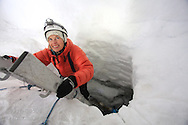 Tourist in April descends by ladder to explore ice cave formed inside glacier by annual meltwaters outside Longyearbyen on Spitsbergen island, Svalbard, Norway.