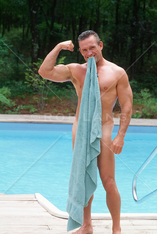 Nude man holding a towel in his mouth to cover his private parts while he makes a muscle by a swimming pool