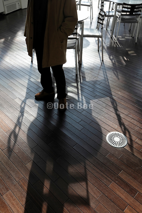 person waiting near empty round tables and chairs