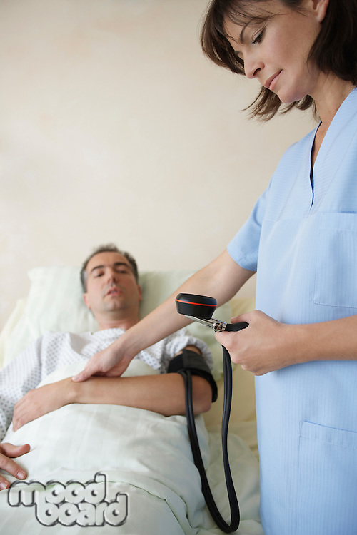 Nurse Taking blood pressure and pulse of patient in hospital bed