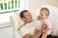 Father and baby on sofa