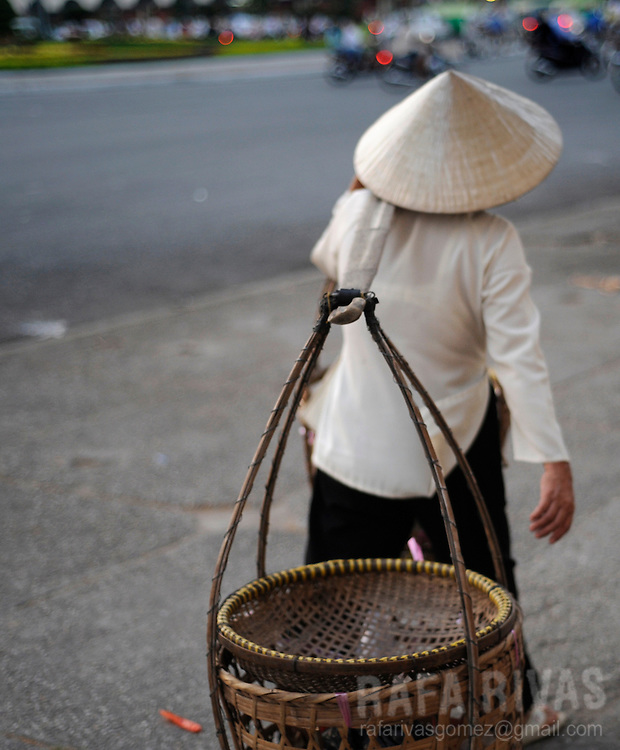 A woman carries baskets in a street of Saigon, Vietnam, on January 2009.