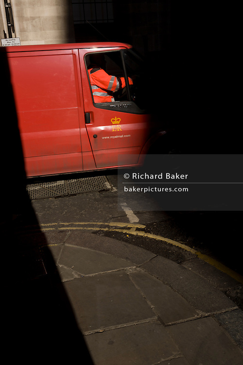 A Post office delivery van driver is caught  in a shaft of early spring light in a side street in the capital's financial district. This is Lombard Street, originally a piece of land granted by King Edward I to goldsmiths from the part of northern Italy known as Lombardy (larger than the modern region of Lombardy). It is a narrow and usually dark sidestreet near the Bank of England in the heart of what is called the Square Mile - the inner-part and oldest quarter of London occupied first by the Romans 2,000 years ago. Nowadays the City of London is home to banks and financial institutions but also with a resident population of under 10,000 but a daily working population of 311,000.
