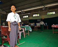 A man controls a quiet poll station in Mandalay on the election day. Photography of ballot boxes is strictly prohibited. Myanmar. 2012