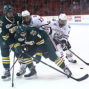 Mike Szmatula #19 of the Northeastern Huskies moves the puck next to opposing players during the game at Matthews Arena on January 18, 2014 in Boston, Massachusetts. (Photo by Elan Kawesch)