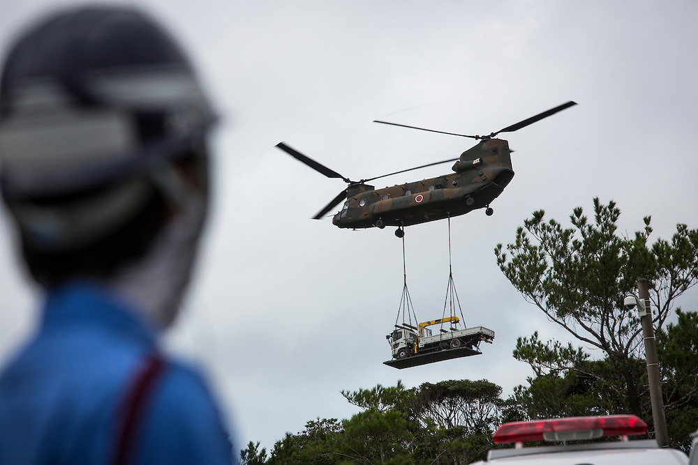 OKINAWA, JAPAN - SEPTEMBER 13 :  A security guard at the gate look at Japan Air Self-Defense Force helicopter Boeing CH-47 after lifting a truck inside of the on going construction of helipads in restricted area of U.S. military's Northern Training Area in the village of Higashi, Okinawa Prefecture, Japan on September 13, 2016. Japanese government uses Japan Self-Defense Forces to help speed up the completion of total six helipads to be use by U.S Military. (Photo by Richard Atrero de Guzman/NURPhoto)