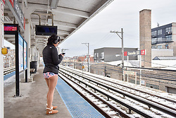 "© Licensed to London News Pictures. 07/01/2018. CHICAGO, USA.  A girl takes part in the annual ""No Pants Subway Ride"", a fun event taking place both in Chicago and worldwide, where people ride the subway wearing no trousers.  With Chicago experiencing an extreme cold snap currently, temperatures made taking part more challenging.  Photo credit: Stephen Chung/LNP"