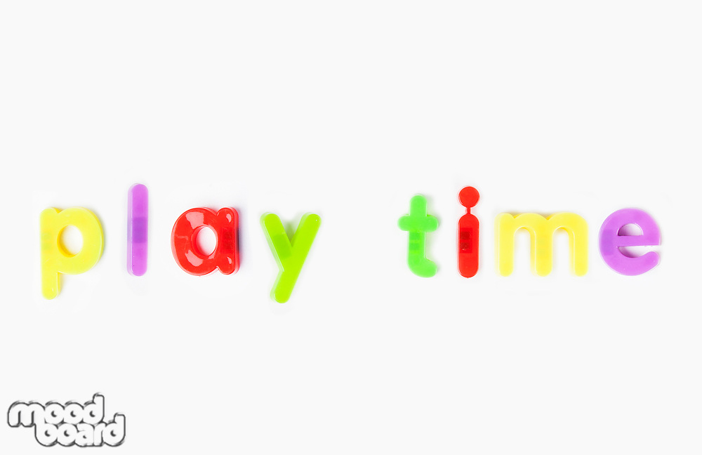 Play time' spelled with alphabet magnets over white background