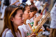 24 SEPTEMBER 2014 - BANGKOK, THAILAND:  Women wearing white for the Vegetarian Festival pray at the Thian Fah Shrine, a Chinese shrine in Bangkok's Chinatown. The Vegetarian Festival is celebrated throughout Thailand. It is the Thai version of the The Nine Emperor Gods Festival, a nine-day Taoist celebration beginning on the eve of 9th lunar month of the Chinese calendar. During a period of nine days, those who are participating in the festival dress all in white and abstain from eating meat, poultry, seafood, and dairy products. Vendors and proprietors of restaurants indicate that vegetarian food is for sale by putting a yellow flag out with Thai characters for meatless written on it in red.     PHOTO BY JACK KURTZ