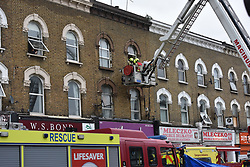© Licensed to London News Pictures. 01/04/2020. London, UK. A patient is lowered to the ground using an aerial platform at an incident involving all emergency services where a suspected COVID-19 case was isolated and removed from their home. Uxbridge Road in Shepherd's Bush was closed for an hour as ambulance, fire brigade and police attended, extracting the patient by crane from a three story apartment building in West London. PPE (personal protective equipment) was in evidence, with the fire brigade using full face respirators normally reserved for firefighting. A police officer commented the Metropolitan police force are issued only with rubber gloves. Ambulance workers decontaminated the scene and reusable equipment before moving on.  Photo credit: Guilhem Baker/LNP