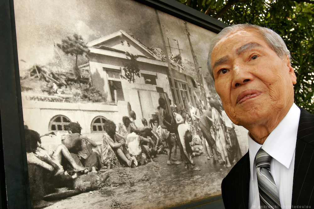 "SUNAO TSUBOI: A-Bomb survivor, standing in front of one of the few pictures taken in the first days of the bombing and in which he can recognize himself between the wounded.  Tsuboi was a 20-year-old university student when he was blown 10 meters into the air by the blast from the bomb and burnt from head to toe. He describes the subsequent scene wandering around the city with eyeballs dangling out of their sockets and skin hanging from bones as a living hell. He wandered for a week and fell into a coma.  When he came to the war was over but he refused to believe it.  ""I thought it was a trick"" He has since suffered three bouts of cancer and tried to commit suicide with his girlfriend when her parents refused to give them permission to marry.  ""We woke up and cried together we were so happy to be alive""."