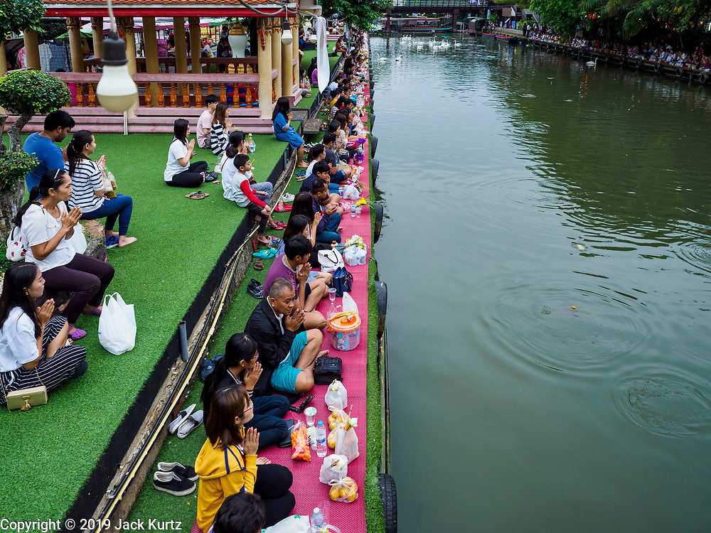 05 JANUARY 2019 - MINBURI, BANGKOK, THAILAND:  People kneel and pray along Khlong Saen Saeb, at the Kwan Riam Floating Market in Minburi, east of downtown Bangkok. People gather on both sides of the khlong (canal) between Wat Bamphen Nuea and Wat Bamphen Tai and monks in boats go past them as people present the monks with food, flowers, and other offerings. It is the only place in Bangkok where monks regularly use boats for their alms rounds.           PHOTO BY JACK KURTZ