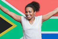 Portrait of young African American woman smiling against South African flag