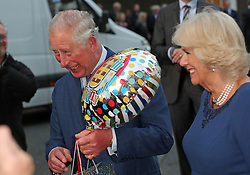 The Prince of Wales holds a birthday gift as he and the Duchess of Cornwall arrive for a tea party at Spencer House in London to celebrate 70 inspirational people marking their 70th birthday this year.