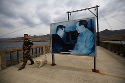 A Chinese soldier and his dog walks past a picture of former Chinese leader Mao Zedong ( R),  and North Korean late leader Kim Il Sung displayed on the Hekou Broken Bridge, which once connected China and North Korea before it was bombed by the US army in the 1950s during the Korean War along Yalu River in Hekou of Dandong Kuandian Manchu Autonomous County, Liaoning Province, China on 06 April 2013. North Korean leader Kim Jong-un has ordered the country's military to increase artillery production, a televised report out of Pyongyang showed 06 April.