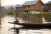 A boy rows a canoe in Nam Pan village, Inle lake, Shan state, Myanmar (Burma).