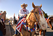 Gil Maken carries with him an American flag signed by co-workers with the Department of State who work with him in Iraq.  Maken took a short leave from his service in Iraq to join his daughters in riding in the Tucson Rodeo Parade, the longest non-motorized parade in the nation. This 89-year-old event occurs each February in conjunction with La Fiesta de los Vaqueros, the Tucson Rodeo.  The event draws over 150,000 spectators in southern Tucson.