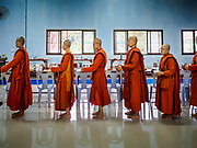 13 JANUARY 2019 - NAKHON PATHOM, THAILAND:  Female monks at Wat Songdhammakalyani line up for breakfast after their morning alms rounds. The Sangha Supreme Council, Thailand's governing body of Buddhist monks, bans the ordination of female monks, but hundreds of Thai women have gone abroad, mostly to Sri Lanka and India, to be ordained. There are about 270 women monks in Thailand and about 250,000 male monks. There are 7 monks and 6 novices at Wat Songdhammakalyani in Nakhon Pathom. It was the first temple in Thailand to have female monks. The temple opened 60 years ago and has always been a temple of women monks. Women can be ordained as novices in Thailand, but to be ordained as a full monk would require the participation of 10 female monks and 10 male monks, and male monks in Thailand are barred from participating in women's ordination ceremonies.    PHOTO BY JACK KURTZ