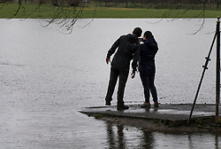© Licensed to London News Pictures. 02/04/2018. London, UK. A couple take a photograph of rising floodwater at Deer Park next to Richmond Lock.  Heavy rain has caused some flooding in areas near the River Thames in the south. Photo credit: Peter Macdiarmid/LNP