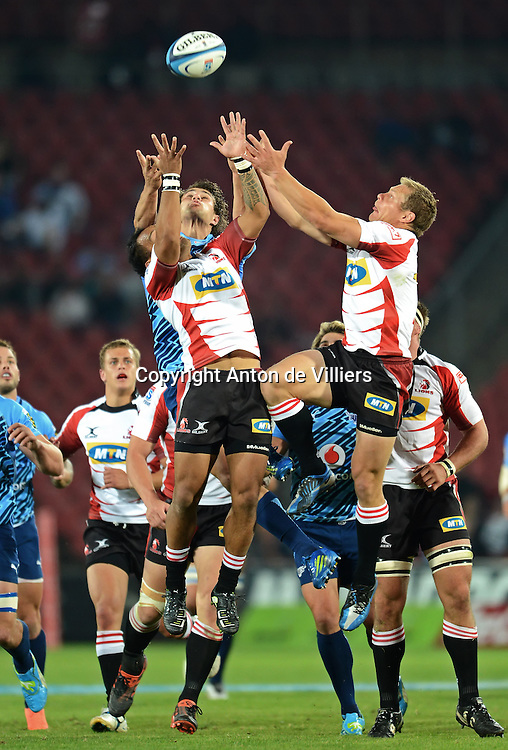 JOHANNESBURG, South Africa, 14 April 2012. James Kamana and Deon van Rensburg of the Lions compete for the ball in the air with JJ Engelbrecht of the Bulls during the Super15 Rugby match between the Lions and the Bulls at Coca-Cola Park in Johannesburg, South Africa on 14 April 2012. The Bulls won this away game 32-18.<br /> Photographer : Anton de Villiers / SASPA