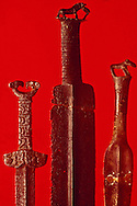 Ancient tribes used animals as symbols on their weapons, clothing and textile patterns.  The Saka dagger on the left, made of metoeorite iron, features Griffins and dates to the 3rd century B.C.  The center dagger features a horse, and the dagger at right a ram, both are bronze from the Semensk-Turbinsk culture in the 12th to 10th centuries B.C.  East Kazakhstan Regional Historical Museum, Oskemen