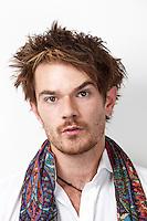 Close-up portrait of suspicious man against white background