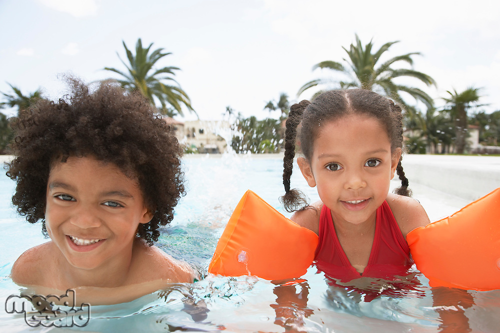Boy (5-6 years) and girl (5-6 years) in swimming pool