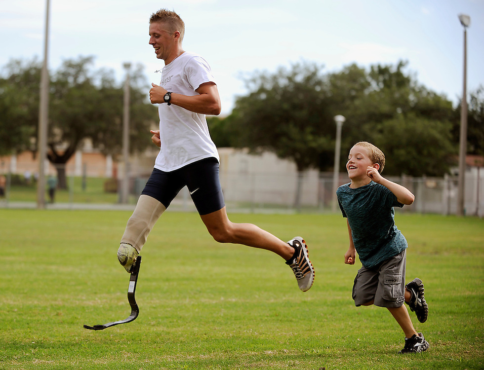 David Prince runs with his son Aidan, 6, during training Wednesday, Aug. 15, 2012 at the University of South Florida. Prince will soon travel to London where he will compete in the Paralympic Games in track.