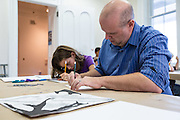 Katherine Cochran-Hill and her father James Hill draw out a stamp design during the Sunday Family Art Encounters at the Kennedy Museum of Art.