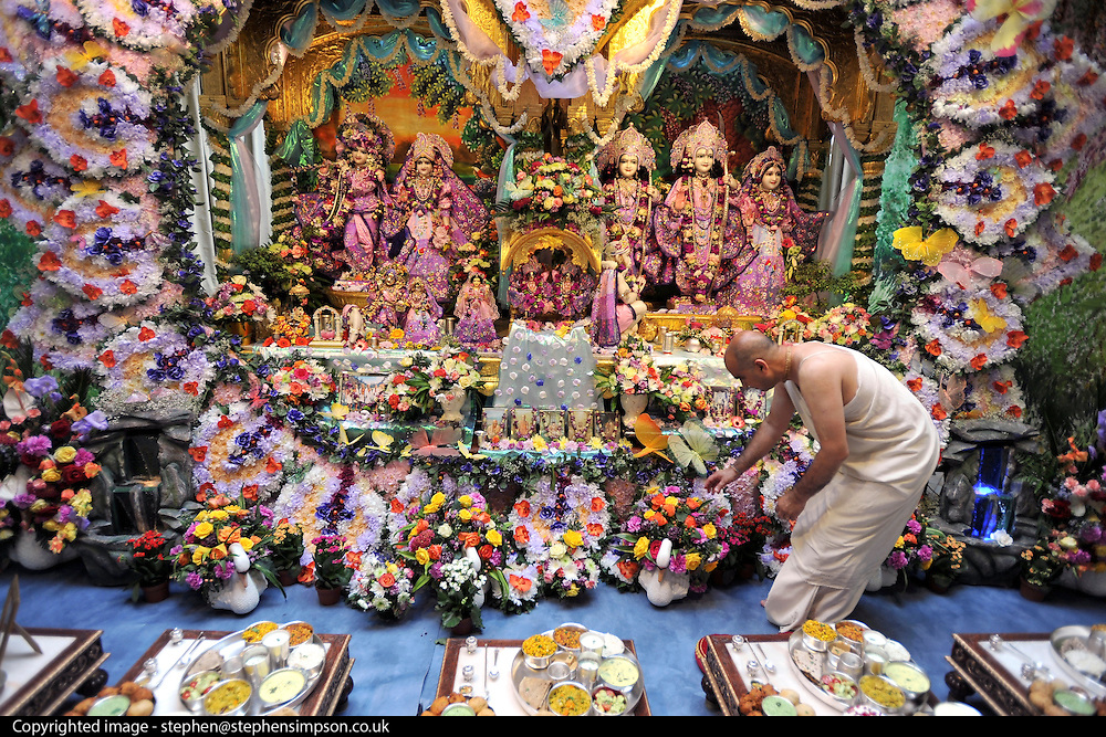 A Pujari tends to the flowers surrounding the deities at the temple at Bhaktivedanta Manor Krishna Temple near Watford on Sunday 5th September 2010 to celebrate Janmashtami the birth of Lord Krishna. The Manor was donated to the Hare Krishna Movement in the early 1970s by former Beatle George Harrison. © under license to London News Pictures.