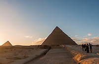 Two Arab couples heading towards the pyramids at Giza near sunset in Egypt.