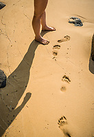 A womans legs and footprints on a sandy beach, Kauai, Hawaii.