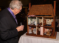 "Joe Bettman takes what may be a final look inside the dollhouse he donated to the silent auction of ""Be a Star,"" the 21st Annual Artemis Center Gala, at Sinclair College's David H. Ponitz Center, Saturday, February 5, 2011.  Bettman says he bought the dollhouse at an auction some 30 years ago, and as his oldest grandchild is now nine years old, there isn't anyone to play with it anymore, ""so it's time it moved on."""