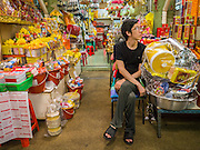 12 OCTOBER 2012 - NAKHON PATHOM, NAKHON PATHOM, THAILAND: A vendor of religious goods waits for customers in the Nakhon Pathom market.   PHOTO BY JACK KURTZ
