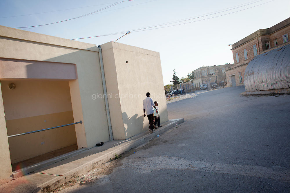 HAL FAR, MALTA - JUNE 21: Immigrants stay outside the containers they live in at the  Hangar Open Center in Hal Far (which translates as &quot;Rat's Town&quot;) on June 21, 2011. The Hangar Open Center is a field with an ex-aircraft hangar which includes Swiss Red Cross tents in a dark, non lit space, and external containers. The conditions are very poor and the has inflamable oil on the floor.<br /> <br /> The Open Centres in Malta serve as a temporary accomodation facility, but they ended becoming permanent accomodation centres, except for those immigrants who receive subsidiary protection or refugee status and that are sent to countries such as the United States, Germany, Poland, and others. All immigrants who enter in Malta illegally are detained. Upon arrival to Malta, irregular migrants and asylum seekers are sent to one of three dedicated immigration detention facilities. Once apprehended by the authorities, immigrants remain in detention even after they apply for refugee status. detention lasts as long as it takes for asylum claims to be determined. This usually takes months; asylum seekers often wait five to 10 months for their first interview with the Refugee Commissioner. Asylum seekers may be detained for up to 12 months: at this point, if their claim is still pending, they are released and transferred to an Open Center.<br /> <br /> <br /> Gianni Cipriano for The New York Times