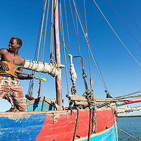Madagascar, Tulear, Young fisherman laughs while playing toy guitar on fishing boat