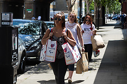 London, June 14th 2017. A fire rages through a residential tower block, Grenfell Tower, in Kensington, West London, with the entire building engulfed in flames. More than 200 firefighters are attending the incident and there are reports of people trapped inside. No figures are available as to casualties. PICTURED: Women head towards a donation centre with bags of goods for the victims.