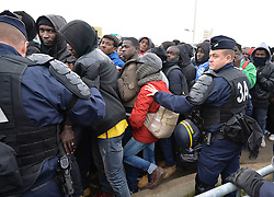 "French police officers push back a large crowd of migrants as they line-up at a processing centre in ""the jungle"" near Calais, northern France, as the mass exodus from the migrant camp begins."