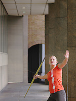 Woman throwing javelin outside building
