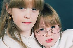 Portrait of two young girls looking thoughtful,