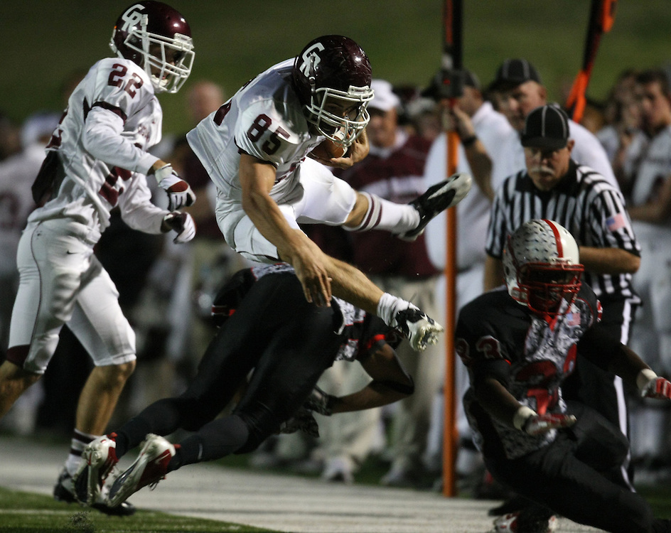 Cinco Ranch's Jake Canfield (85) leaps over Bellaire's Khari Sharif during the first half of a high school football playoff game, Saturday, November 1, 2011 at Tully Stadium in Houston, TX.